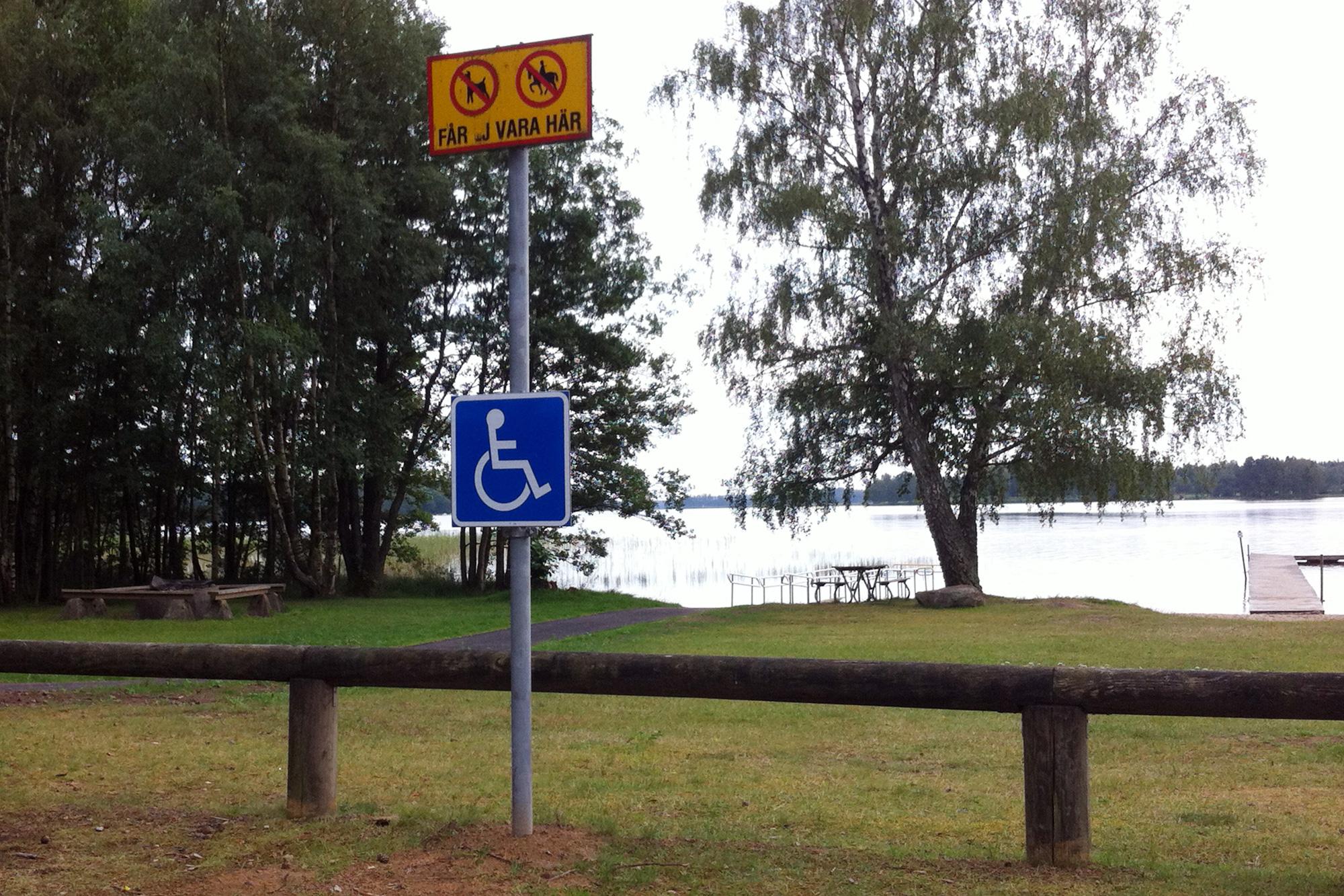 Rollstuhlpiktogramm auf einem Parkplatz, mit unpassierbarem Zaun dahinter
