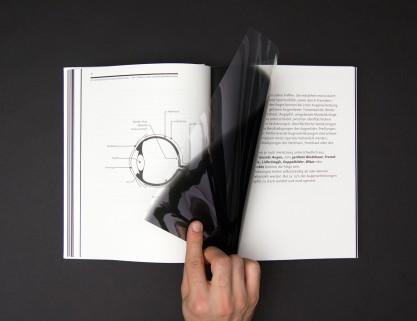 Aufgeschlagene Doppelseite aus dem Theoriebuch: Kapitel: So unterschiedlich kann Sehen sein, die bedruckte Simulationsfolie wird umgeschlagen.