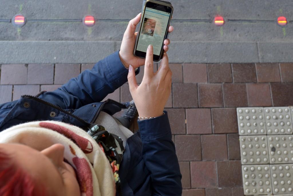 Frau mit Handy in der Hand blickt auf Straße mit integrierten Leuchtpunkten